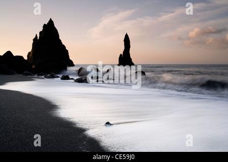 Lavaggio onde in circa nera vulcanica di pile di mare sulla costa di Vik in Islanda Foto Stock
