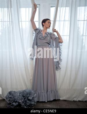 Una donna che indossa un lungo abito grigio, in piedi di fronte a una finestra