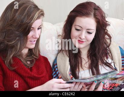Due ragazze adolescenti di età compresa tra 15 anni guardando una celebrità rivista mentre seduto su un divano a Foto Stock