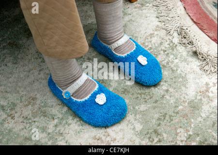 Donna anziana di indossare i calzini e pantofole in maglia per mantenere caldo e accogliente in inverno Foto Stock