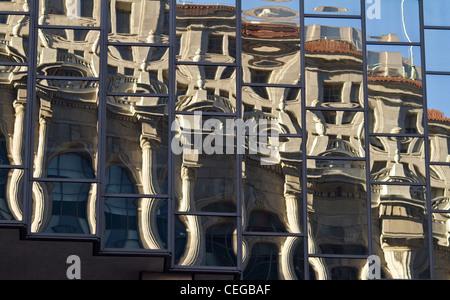 Distorto i riflessi di un edificio in stile neoclassico si riflette nelle finestre di un vetro moderno alto edificio. Foto Stock