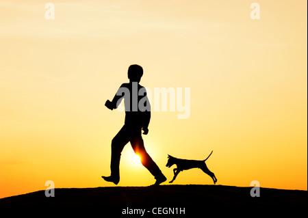 Silhouette di un giovane ragazzo indiano correre e giocare con il suo cucciolo. India Foto Stock