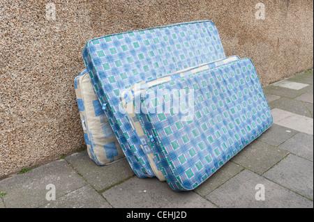 Vecchi materassi oggetto di dumping nella Street, London, England, Regno Unito Foto Stock