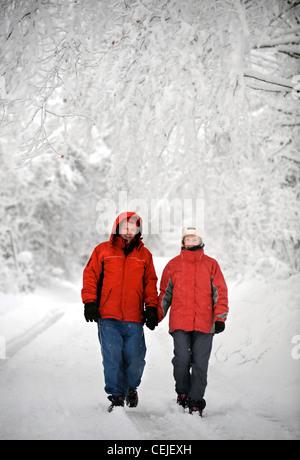 Un paio di matching red cappotti invernali a camminare in una corsia di Cotswold in condizioni nevoso REGNO UNITO Foto Stock