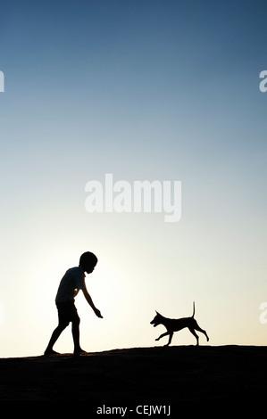 Silhouette di un giovane ragazzo indiano giocando con il suo cucciolo. India Foto Stock