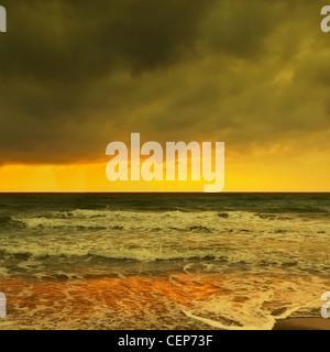 Onde che si infrangono sulla spiaggia wintery all'alba; Spagna Foto Stock