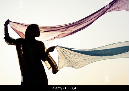 Ragazza indiana con star veli modellata dal vento. Silhouette Foto Stock