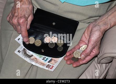 Le mani di una signora anziana conteggiare denaro in sterline banconote e monete Foto Stock