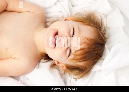 Bambino felice ridendo e posa in fogli bianchi Foto Stock