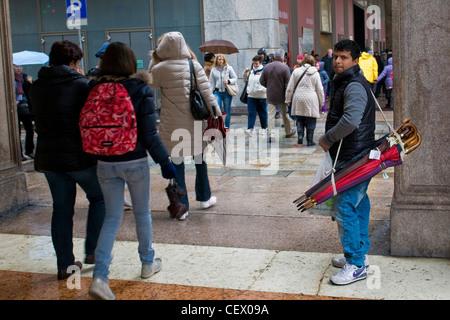 Immigrati bengalesi che vende ombrelli, Milano, Italia Foto Stock
