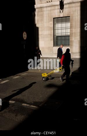 Uomo di consegna recante un carrello passeggiate attraverso un albero di primavera la luce in una strada laterale Foto Stock