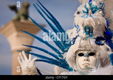 Un uomo vestito in costume di carnevale punti presso la statua del leone di San Marco, Piazza Venezia, Italia Foto Stock