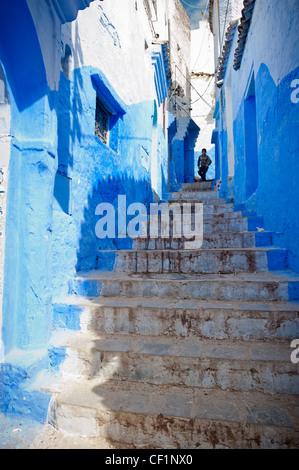 Ragazzo giovane scendendo le scale in una delle strade del blu medina murata di Chefchaouen, Marocco Foto Stock