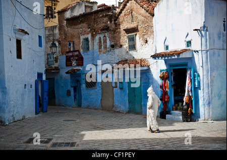 Uomo musulmano camminando nel blu walled vecchia medina di Chefchaouen, Marocco