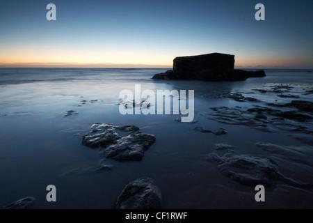 Una scatola di pillole sulla spiaggia all'Naze nei primi albori della luce. Foto Stock