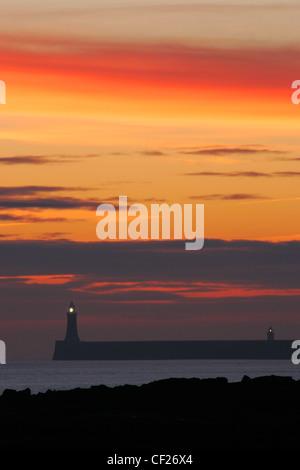 Sunrise guardando verso nord Tyne Pier e il faro in Tynemouth. Foto Stock