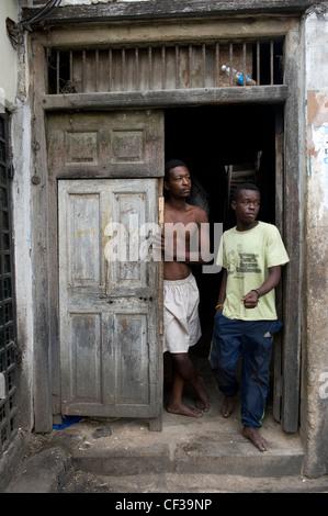 Gli uomini in piedi in una porta di ingresso Stone Town Zanzibar Tanzania Foto Stock