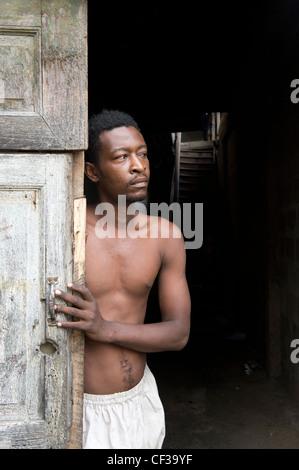 Uomo in piedi in una porta di ingresso Stone Town Zanzibar Tanzania Foto Stock