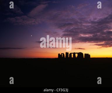 Un ampio panorama di Stonehenge trilithons stagliano dopo il tramonto e il sorgere della luna. Foto Stock