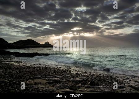 Raggi di sole lo scoppio attraverso nuvole temporalesche su Mumbles punto all'alba. Foto Stock