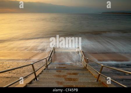 Le onde impetuose sulla spiaggia su passi all'alba sul lungomare a Exmouth. Foto Stock