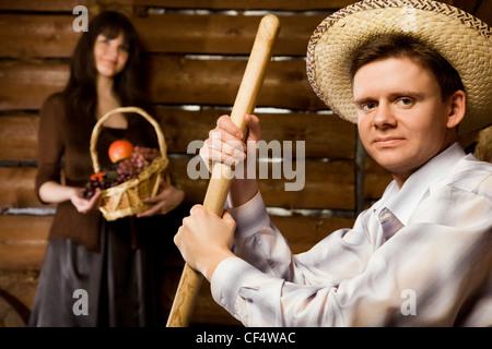 Uomo sorridente forcone cappello di paglia seduta panca in legno capanna  log giovane donna cesto frutta 753904223e24