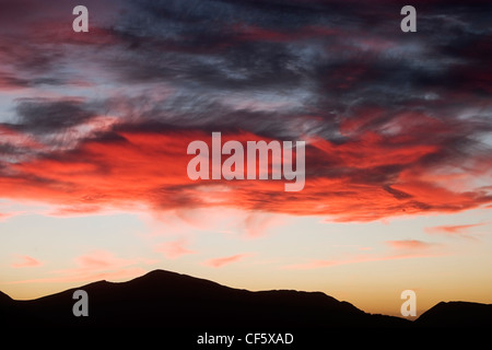 Rosso infuocato nuvole illuminano il cielo di sera sopra le colline di Keswick nel distretto del lago. Il nome 'Keswick' Foto Stock