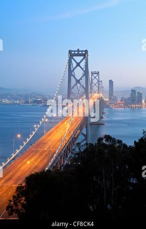 Stati Uniti, California, San Francisco, Oakland Bay Bridge al tramonto e dello skyline della città Foto Stock