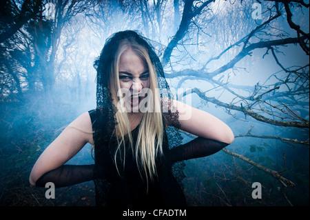Un giovane attraente bionda donna vampiro nella foresta di bosco Foto Stock