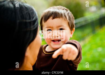 Una madre trattiene e bacia il figlio di 2 anni.