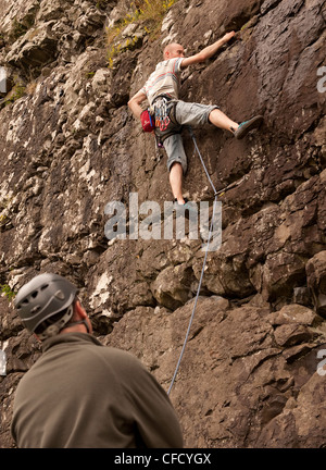 Un scalatore si avvicina alla roccia bagnata su un percorso di sport in Benny Beg, Scozia, mentre i suoi orologi Foto Stock