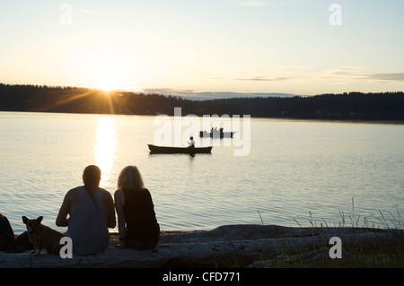 Silhouette di un giovane con il cane a guardare il tramonto a Lisabeula Beach, Vashon Island, nello Stato di Washington, Foto Stock