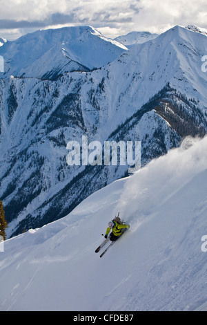 Un giovane maschio sciatore barre una polvere girare appena fuori dai limiti a Kicking Horse Resort, Golden, Britsh Foto Stock