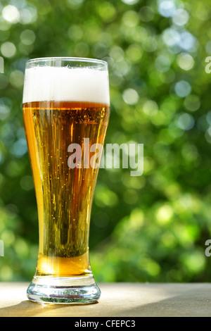 Bicchiere da birra al tavolo di close-up, lo sfondo è al di fuori della messa a fuoco Foto Stock