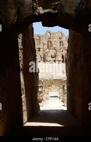 Attraverso un arco dell'arena ellittica e interno del magnifico color miele antico anfiteatro romano a El Jem Foto Stock