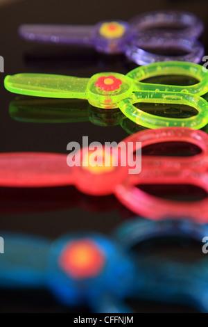 Vivacemente colorato per bambini forbici su sfondo nero Foto Stock