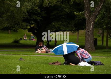 Un paio di nascondere sotto un ombrello con la bandiera scozzese decorarla in Kelvingrove Park a Glasgow Foto Stock