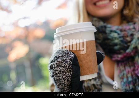 Stati Uniti d'America, nello Stato di New York, New York, Brooklyn, donna indossa guanti holding tazza da caffè Foto Stock