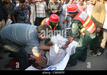 Funzionari di salvataggio di spostamento del corpo morto di un uomo chiamato Ghulam Akbar sulla barella che morì sul posto colpito da Busco Transit Bus quando era sulla strada per la sua bici del motore in corrispondenza di Shimla Hill a Lahore giovedì 18 ottobre, 2012.