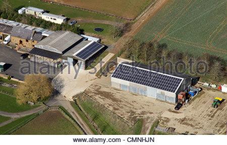 Vista aerea di una fattoria con pannelli solari su due edifici di granaio Foto Stock