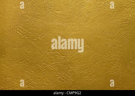 La texture di un muro di cemento rivestito con vernice dorata Foto Stock
