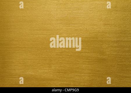 La texture di un muro di cemento rivestito con vernice dorata con lunghi tratti Foto Stock