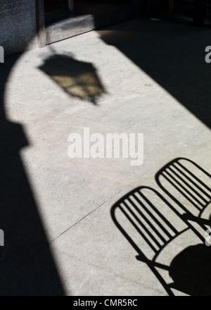 Lampione ombra e café sedie gettano ombre sul marciapiede - Torino, Italia Foto Stock