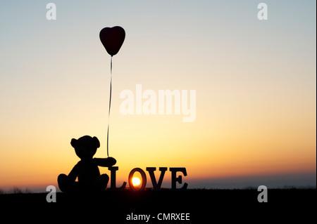 Orsacchiotto di peluche tenendo a forma di cuore pallone avanti anche la parola amore a sunrise Foto Stock