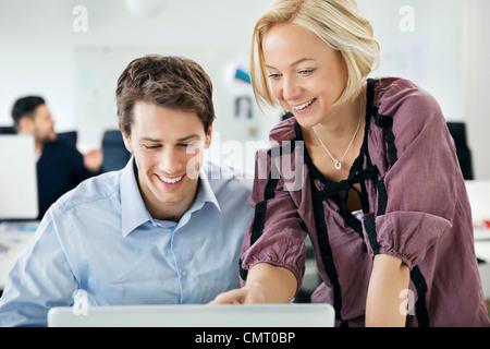 Due persone che si aiutano reciprocamente in ufficio Foto Stock