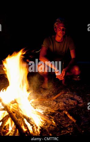 Uomo seduto accanto al fuoco