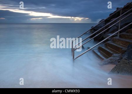 Lavaggio onde su gradini che conduce al mare. Machans Beach, Cairns, Queensland, Australia Foto Stock
