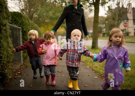 Donna con quattro bambini camminando lungo il marciapiede Foto Stock