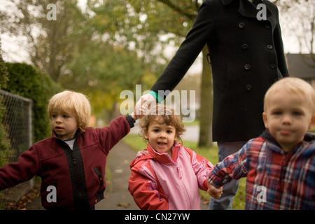 Donna con tre bambini camminando lungo il marciapiede Foto Stock