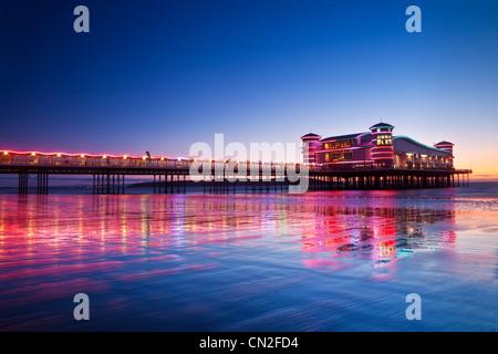 Twilight oltre il Grand illuminato dal molo Weston-Super-Mare, Somerset, Inghilterra, Regno Unito riflessa nella sabbia bagnata a marea alta. Foto Stock
